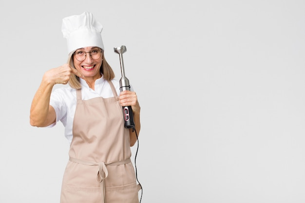 Vrouw van middelbare leeftijd bakker met een mixer op kopie ruimte muur