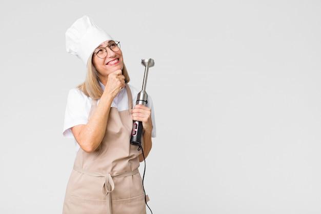 Vrouw van middelbare leeftijd bakker met een mixer op kopie ruimte muur Premium Foto