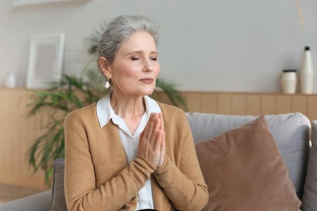 Vrouw van middelbare leeftijd bidden, ogen geopend, opkijkend, hopend op het beste, om vergeving vragen.