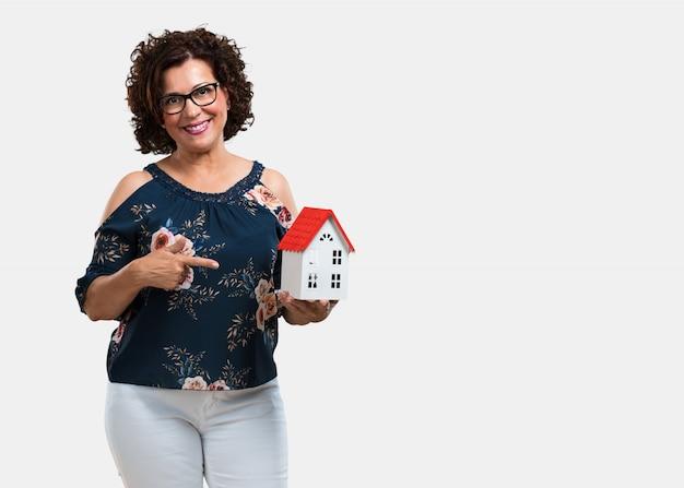 Vrouw van middelbare leeftijd blij en zelfverzekerd, toont een miniatuur huismodel