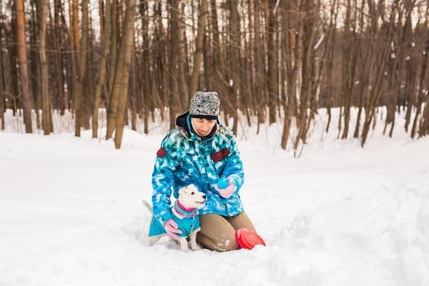 Vrouw van middelbare leeftijd buitenshuis met schattige hond - jack russell terrier in winterseizoen