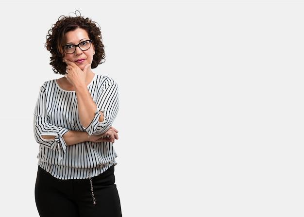 Vrouw van middelbare leeftijd denken en opzoeken, verward over een idee