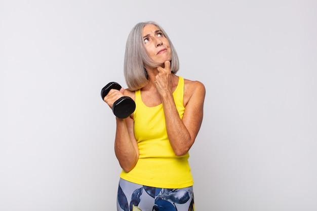 Vrouw van middelbare leeftijd denkt, voelt zich twijfelachtig en verward, met verschillende opties, zich afvragend welke beslissing ze moet nemen. fitnessconcept