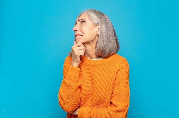 Vrouw van middelbare leeftijd denkt, voelt zich twijfelachtig en verward, met verschillende opties, zich afvragend welke beslissing ze moet nemen