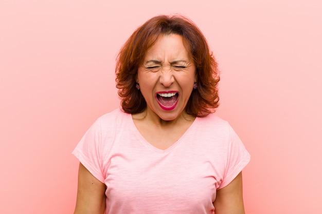 Vrouw van middelbare leeftijd die agressief schreeuwt, erg boos, gefrustreerd, verontwaardigd of geïrriteerd, nee schreeuwend tegen de roze muur
