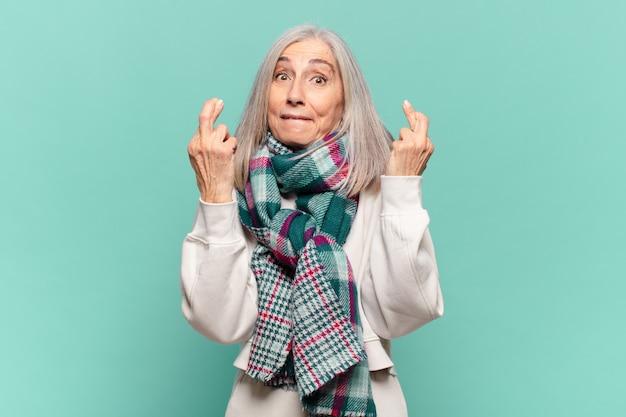 Vrouw van middelbare leeftijd die angstig vingers kruist en hoopt op veel geluk met een bezorgde blik