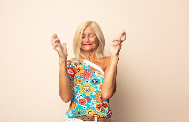 Vrouw van middelbare leeftijd die angstig vingers kruist en op geluk hoopt met een bezorgde blik