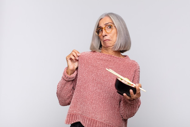 Vrouw van middelbare leeftijd die arrogant, succesvol, positief en trots kijkt, wijzend naar zelf aziatisch voedselconcept