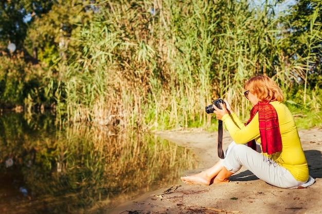 Vrouw van middelbare leeftijd die beelden controleert op camera's die aan de oever van de herfstrivier zitten. senior vrouw die geniet van de natuur en hobbyfoto's maakt