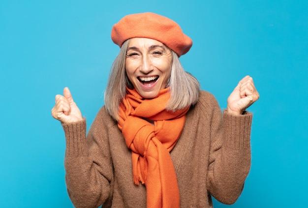 Vrouw van middelbare leeftijd die buitengewoon blij en verrast kijkt, succes viert, schreeuwt en springt