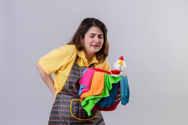 Vrouw van middelbare leeftijd die de emmer van de schortholding met het schoonmaken van hulpmiddelen draagt die onwel kijkt wat betreft haar rug met pijn die zich over witte muur bevindt