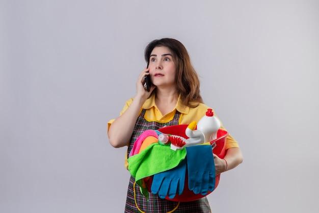 Vrouw van middelbare leeftijd die de emmer van de schortholding met het schoonmaken van hulpmiddelen draagt die verbaasd kijken terwijl het spreken op mobiele telefoon die zich over witte muur bevindt
