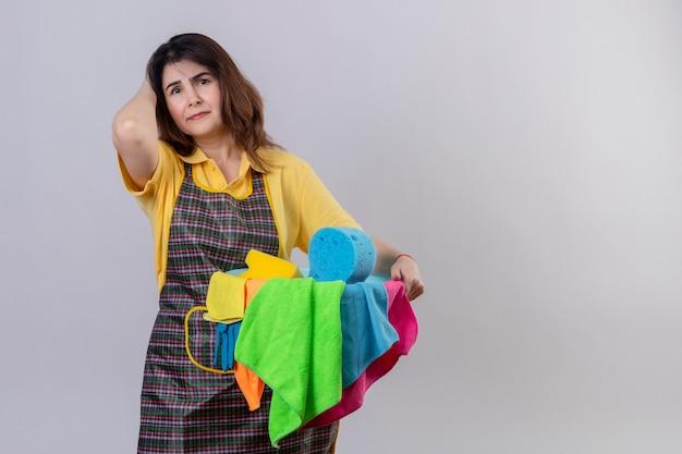 Vrouw van middelbare leeftijd die de emmer van de schortholding met het schoonmaken van hulpmiddelen draagt die vermoeid en overwerkt status over witte muur kijken