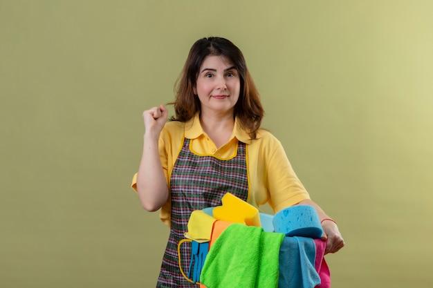 Vrouw van middelbare leeftijd die de emmer van de schortholding met het schoonmaken van hulpmiddelen draagt die vuist opheft die haar succes het glimlachen verheugt kijkend zeker status over groene muur