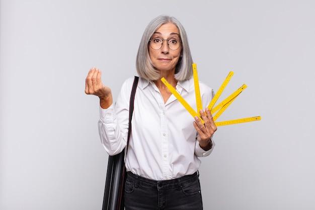 Vrouw van middelbare leeftijd die een capice of geldgebaar maakt en u zegt uw schulden te betalen !. architect concept