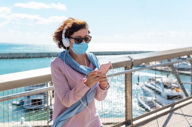 Vrouw van middelbare leeftijd die een gezichtsmasker draagt dat op een brug staat en naar muziek luistert