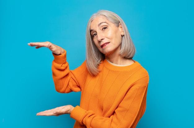 Vrouw van middelbare leeftijd die een voorwerp met beide handen op zijexemplaarruimte houdt, een voorwerp toont, aanbiedt of adverteren