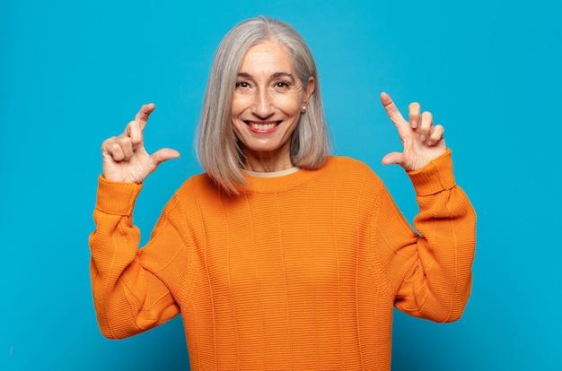 Vrouw van middelbare leeftijd die eigen glimlach met beide handen inlijsten of schetst, er positief en gelukkig uitziet, wellness-concept