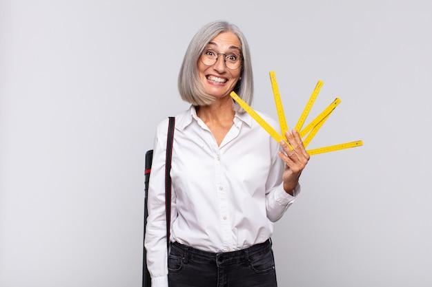 Vrouw van middelbare leeftijd die er blij en aangenaam verrast uitzag, opgewonden met een gefascineerde en geschokte uitdrukking. architect concept
