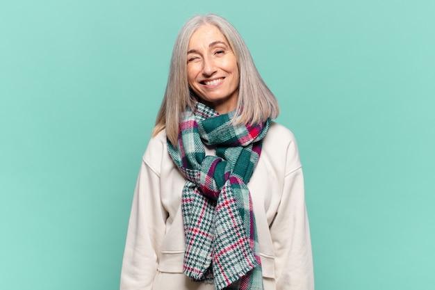 Vrouw van middelbare leeftijd die er gelukkig en vriendelijk uitziet, lacht en je met een positieve houding aankijkt