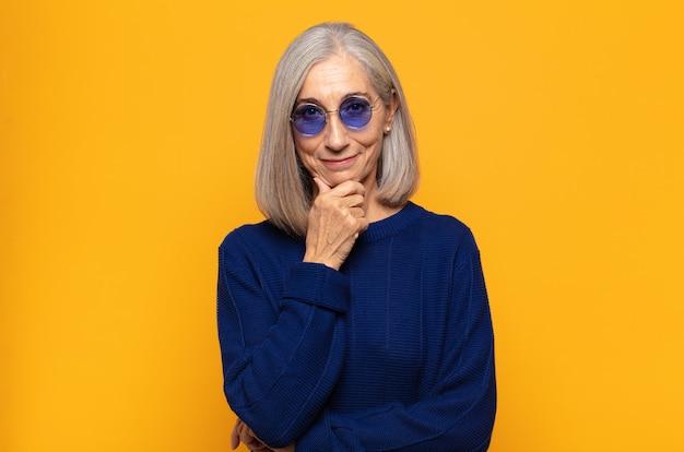 Vrouw van middelbare leeftijd die er gelukkig uitziet en lacht met de hand op de kin, zich afvraagt of een vraag stelt, opties vergelijkt