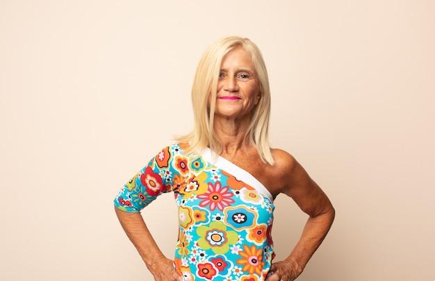 Vrouw van middelbare leeftijd die er gelukkig, vrolijk en zelfverzekerd uitziet, trots lacht en naar de andere kant kijkt met beide handen op de heupen