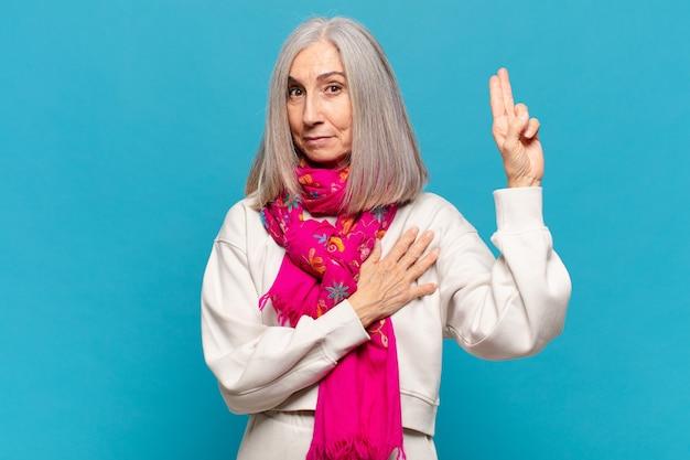 Vrouw van middelbare leeftijd die er gelukkig, zelfverzekerd en betrouwbaar uitziet, glimlacht en een overwinningsteken toont, met een positieve instelling