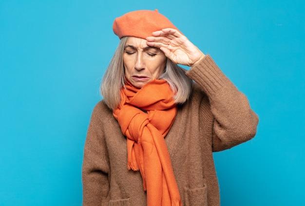 Vrouw van middelbare leeftijd die er gestrest, moe en gefrustreerd uitziet, het zweet van het voorhoofd droogt, zich hopeloos en uitgeput voelt