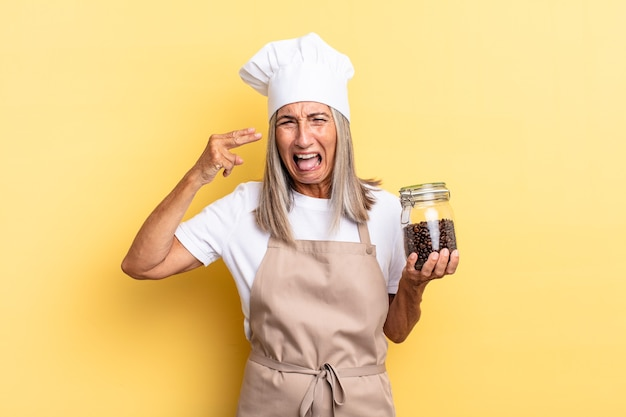 Vrouw van middelbare leeftijd die er ongelukkig en gestrest uitziet, zelfmoordgebaar maakt een pistoolteken met de hand, wijzend naar het hoofd met koffiebonen