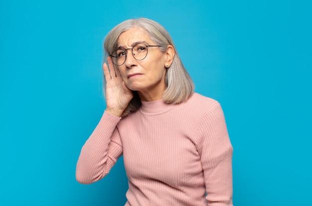 Vrouw van middelbare leeftijd die er serieus en nieuwsgierig uitziet, luistert, probeert een geheim gesprek of roddel te horen, afluistert
