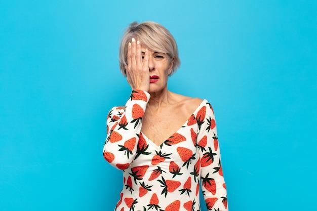Vrouw van middelbare leeftijd die er slaperig, verveeld en geeuwend uitziet, met hoofdpijn en één hand die het halve gezicht bedekt
