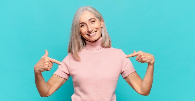 Vrouw van middelbare leeftijd die er trots, arrogant, blij, verrast en tevreden uitziet, naar zichzelf wijst en zich een winnaar voelt