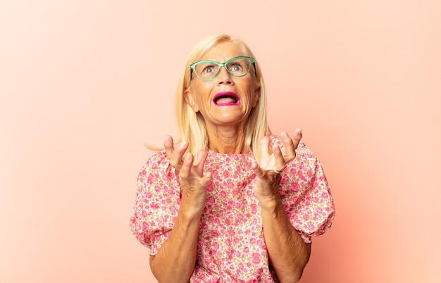 Vrouw van middelbare leeftijd die er trots, positief en casual uitziet en met beide handen naar de borst wijst