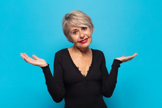 Vrouw van middelbare leeftijd die er verbaasd, verward en gestrest uitziet, zich afvraagt tussen verschillende opties, zich onzeker voelt