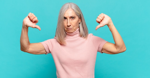 Vrouw van middelbare leeftijd die er verdrietig, teleurgesteld of boos uitziet, duimen naar beneden toont in onenigheid, zich gefrustreerd voelt
