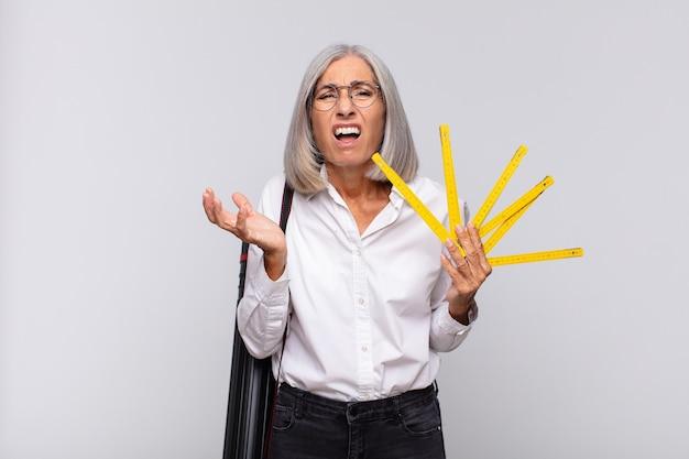 Vrouw van middelbare leeftijd die er wanhopig en gefrustreerd, gestrest, ongelukkig en geïrriteerd uitziet, schreeuwend en schreeuwend. architect concept