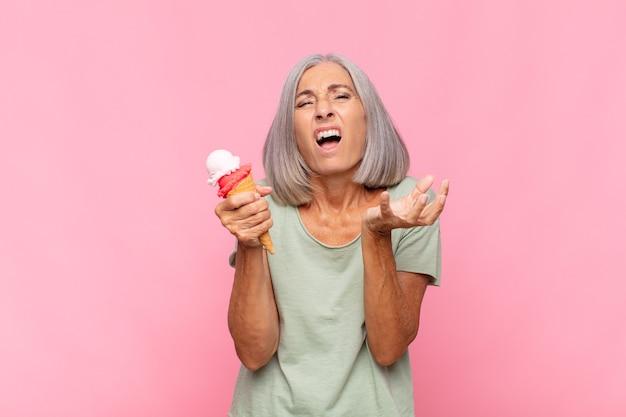 Vrouw van middelbare leeftijd die er wanhopig en gefrustreerd, gestrest, ongelukkig en geïrriteerd uitziet, schreeuwend en schreeuwend met een ijsje
