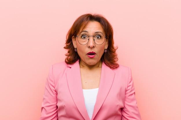 Vrouw van middelbare leeftijd die erg geschokt of verrast kijkt, starend met open mond en wauw zegt