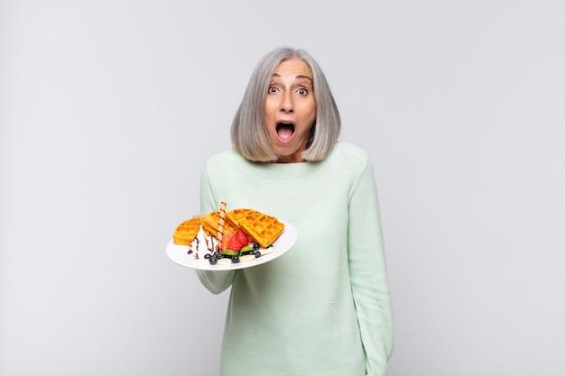 Vrouw van middelbare leeftijd die erg geschokt of verrast kijkt, starend met open mond en zegt wow. ontbijt concept