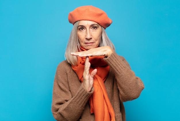 Vrouw van middelbare leeftijd die ernstig, streng, boos en ontevreden kijkt, time-outteken maakt