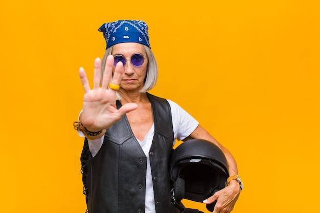 Vrouw van middelbare leeftijd die ernstig, streng, ontevreden en boos kijkt en open palm toont die stopgebaar maakt