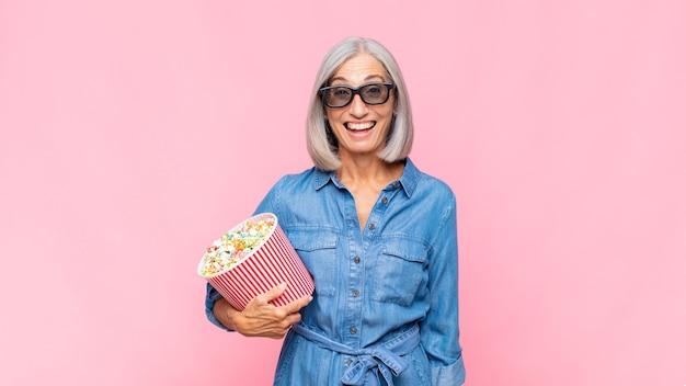 Vrouw van middelbare leeftijd die gelukkig en aangenaam verrast, opgewonden geïsoleerd kijkt