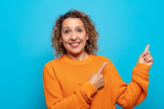 Vrouw van middelbare leeftijd die gelukkig glimlacht en naar kant en naar boven richt met beide handen die voorwerp in exemplaarruimte tonen