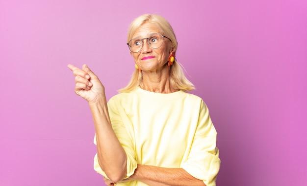 Vrouw van middelbare leeftijd die gelukkig glimlacht en zijwaarts kijkt, zich afvraagt, denkt of een idee heeft