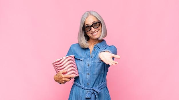 Vrouw van middelbare leeftijd die gelukkig glimlacht met een vriendelijke, zelfverzekerde, positieve blik, een object of conceptfilmconcept aanbiedt en toont
