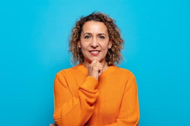 Vrouw van middelbare leeftijd die gelukkig kijkt en met hand op kin glimlacht, zich afvraagt of een vraag stelt, opties vergelijkt