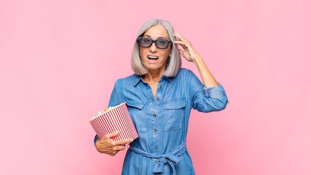 Vrouw van middelbare leeftijd die gelukkig, verbaasd en verrast geïsoleerd kijkt