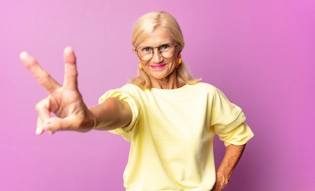 Vrouw van middelbare leeftijd die gelukkig, zorgeloos en positief glimlacht en kijkt, met één hand overwinning of vrede gebaart