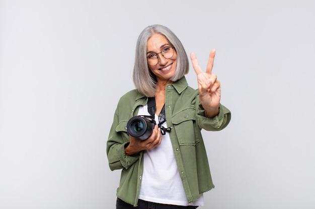 Vrouw van middelbare leeftijd die gelukkig, zorgeloos en positief glimlacht en kijkt, overwinning of vrede met één hand gebaart. fotograaf concept
