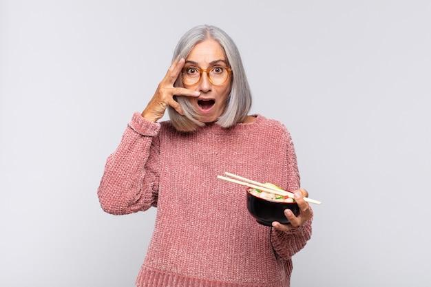 Vrouw van middelbare leeftijd die geschokt, bang of doodsbang kijkt, gezicht bedekt met hand en gluren tussen vingers aziatisch eten concept